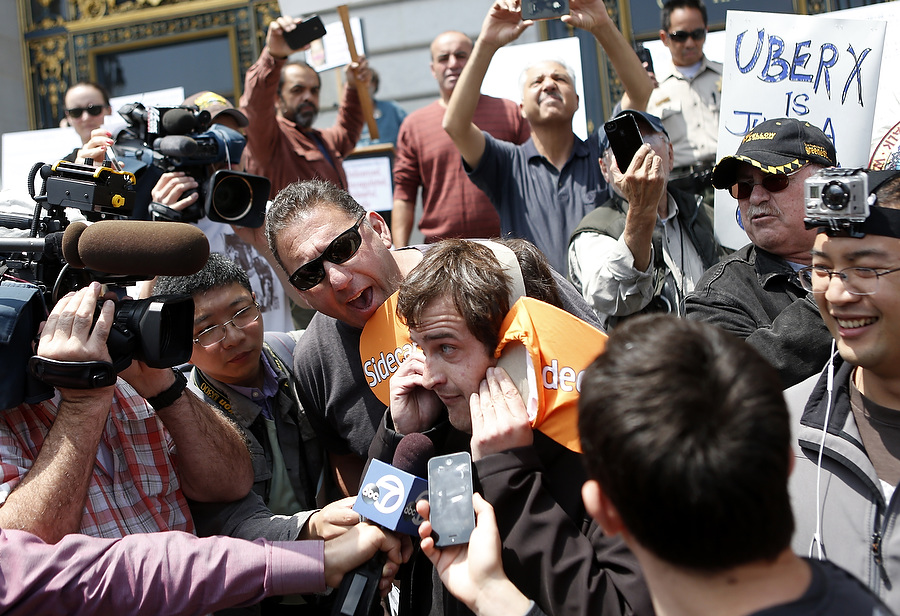 Sidecar driver Teddy Ordon (center)attempts to answer questions while San Francisco taxi drivers voice their opposition against ride sharing programs taxi drivers say are operating illegally in San Francisco, California, July 30, 2013.   REUTERS/Beck Diefenbach   (UNITED STATES)